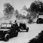 Presun delostrelcov 1. čs. armádneho zboru. Za americkým vozidlom Jeep Willys v popredí fotografie je pravdepodobne ťahaný sovietsky ľahký 45mm pechotný kanón vz. 37